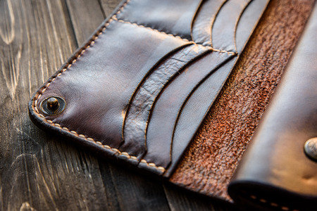Brown leather wallet on wooden table, Old leather wallet. Stock Photo