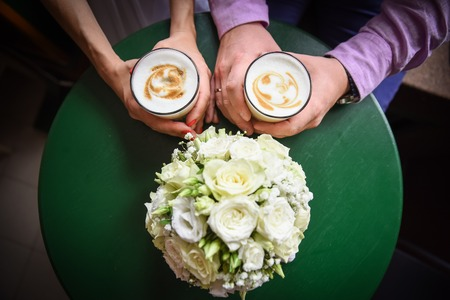 Man and woman hands and coffee cups on the table.