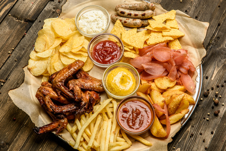 plato del buen comer: a wide selection of snacks for beer on a parchment top view. Foto de archivo
