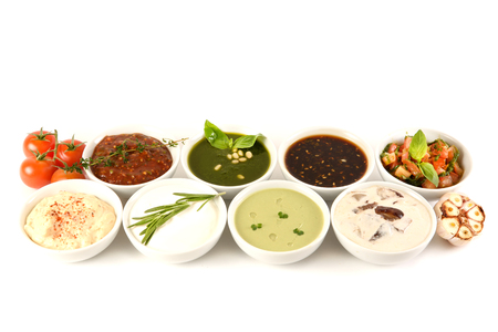 Set of 8 savory sauces and toppings isolated on white. Spoons dipped in the sauces. Soy sauce, curry, mustard, barbecue sauce. Set for menu. top view Stock Photo