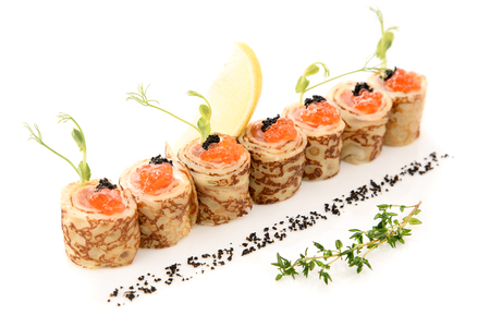 blini: pancakes with red caviar and salmon on a white background served with lemon and dried black olives. Stock Photo
