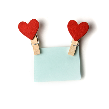 clothespins with red hearts holding a blue sticker Stock Photo