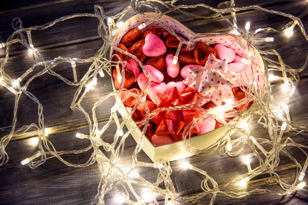 perle: The concept of Valentines Day with a garland and gift box in the shape heart on wooden background.