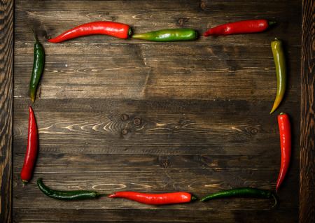 hottest: Red and green chili pepper on plate on wooden background