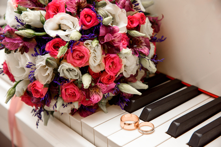 wedding bouquet and ring lying on white piano Stock Photo