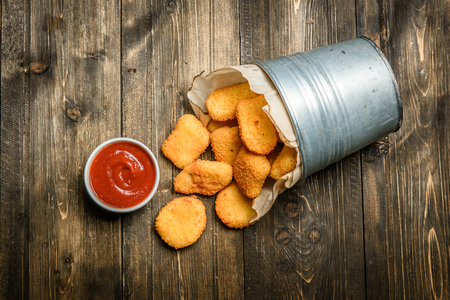 From above metal basket with chicken nuggets and sauce on wooden background.