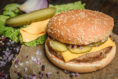 Horizontal studio shot of cheese and pickled cucumber placed at appetizing hamburger on wooden table.
