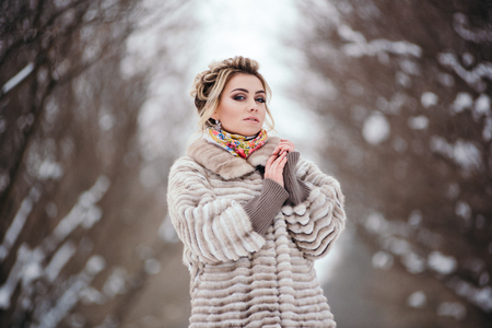 Beautiful girl in fur coat in winter in the forest
