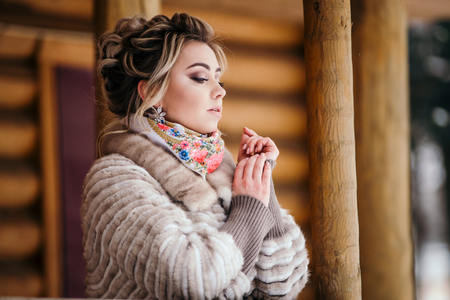 Beautiful girl in fur coat at a wooden house