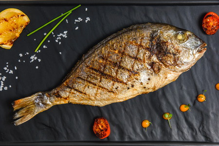 Tasty fish with vegetables and lemon on black plate