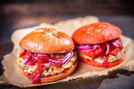 Frische zwei hausgemachte Burger auf Holzbrett über dunklem Holzhintergrund.