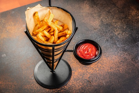 French fries in a paper bag with sauces. Top view.