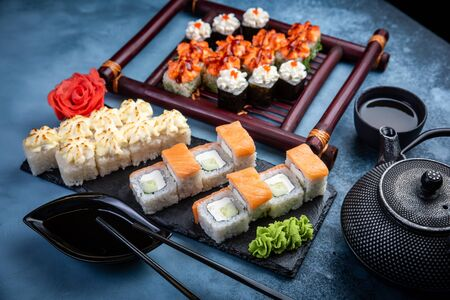 From above composition of various sushi rolls, green tea and chopsticks on marble background