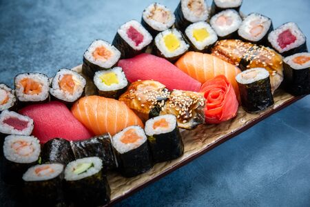 Top view of traditional delicious Japanese seafood served on wooden board on dark marble background Stock Photo