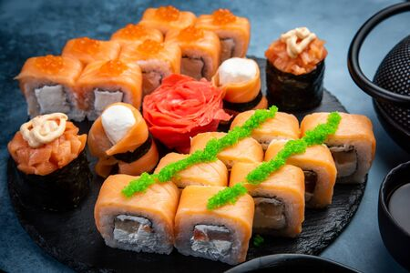 From above composition of delicious Japanese rolls topped with wasabi arranged on dark marble background