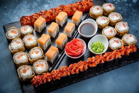 From above composition of sushi, rolls, soy sauce, ginger and wasabi served on black wooden board Stock Photo