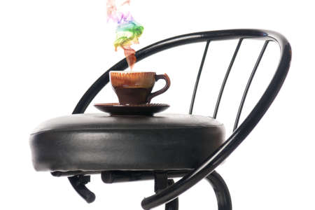 Coffee cup on a bar chair with a colour smoke. Isolated over white. Stock Photo