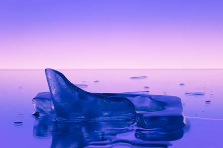 Iceberg and water drops on a mirror surface on a smooth background.