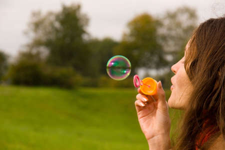 Cute girl blowing bubbles outdoors (close up)
