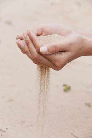 Sand flows through female fingers