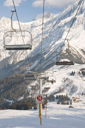 four peaks wilderness: Four chair lifts on the Alps background. Stock Photo