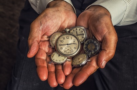horologe: clock in the hands of an old man, a handful of hours Stock Photo