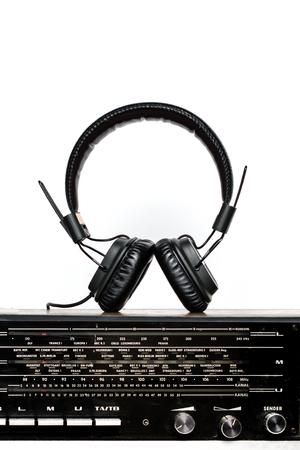 old radio with headphones on white background