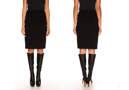 female legs in a skirt and  boots on a white background