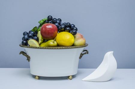 food still: ceramic vase with fruit  and bird figurine