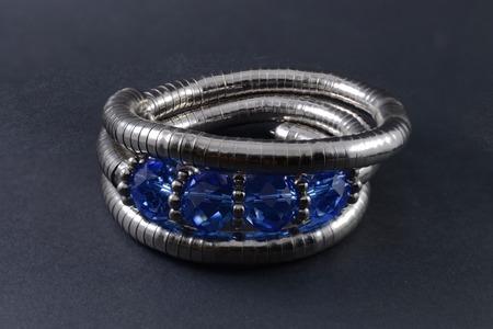 armlet: iron bracelet with blue stones isolated on black Stock Photo