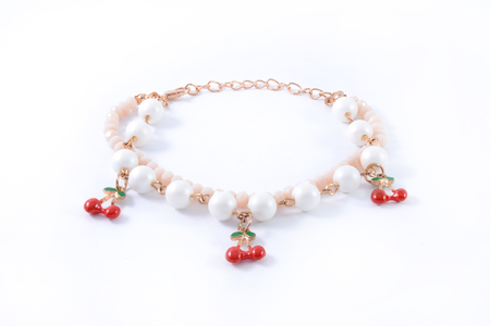 pendants: bracelet with pearls and pendants isolated on white