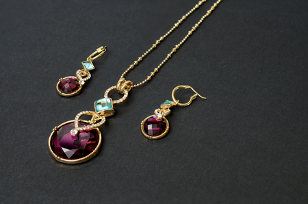pendant with earrings on a black background