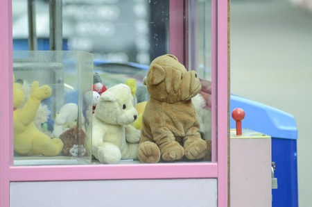 grabbing back: Sad soft toys in slot machine, concept homeless