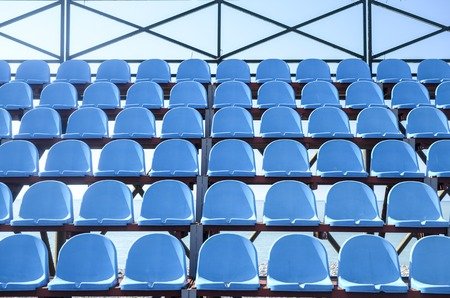 unoccupied: Rows of blue plastic seats in the stadium