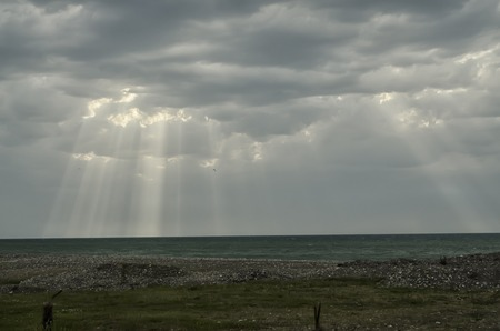 suns: The suns rays passing through the storm clouds over the sea