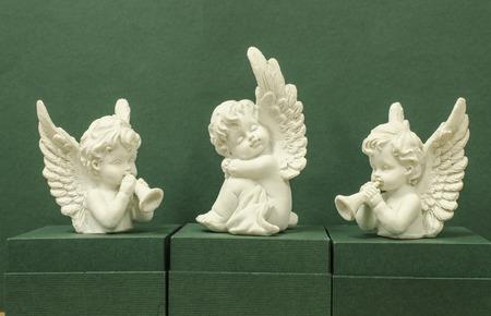 cherubs: Three angels on a green background