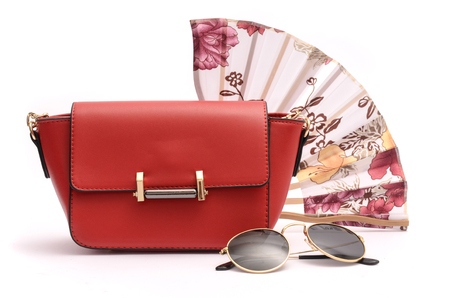 Red leather clutch sunglasses and hand fan, still life