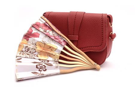 Red leather clutch and hand fan still life