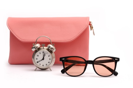 Pink leather clutch, alarm clock and sunglasses still life Stock Photo