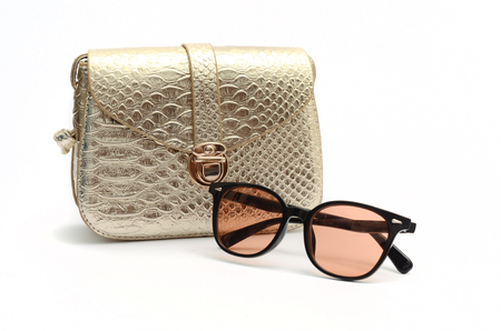 Golden clutch and sunglasses still life