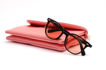 Pink leather clutch and sunglasses still life