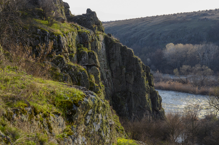 Landscape with a cliff covered with green grass. Фото со стока