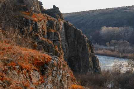 Landscape with a cliff covered with red grass. Stock Photo