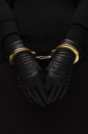 arrestment: Golden handcuffs leather black gloves, concept Stock Photo