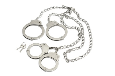 Handcuffs on the hands and feet Stock Photo