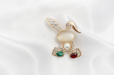 Golden brooch bunny with diamonds and moonstone on silk fabric