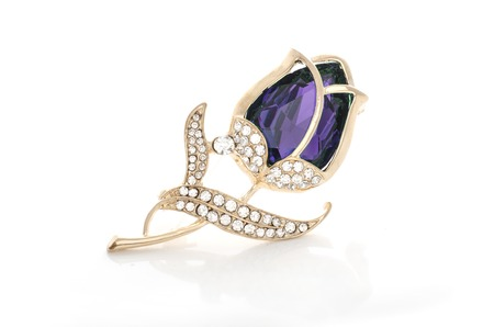 gold brooch rose bud with purple stone and diamonds isolated on white