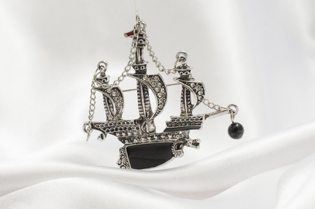 silver brooch ship with diamonds isolated on white silk