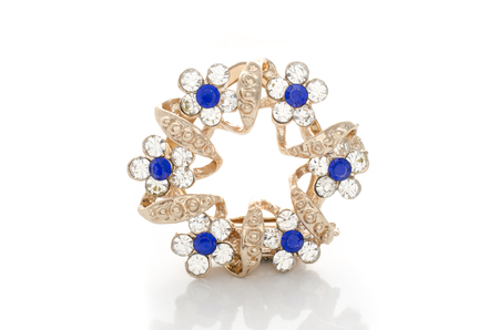 gold round brooch with diamonds and sapphires isolated on white