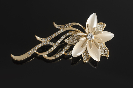gold brooch flower with moon stone isolated on black